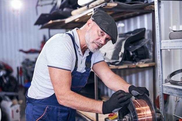 Beau mécanicien utilisant du fil de cuivre dans un atelier de réparation de véhicules