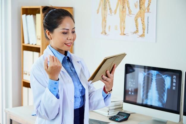 Beau médecin asiatique à l'aide de pad