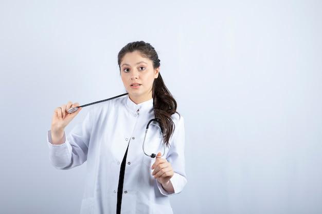 Beau médecin en blouse blanche à la surprise sur un mur blanc.