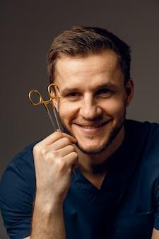 Beau médecin avec gros plan de ciseaux chirurgicaux. homme confiant tenant du matériel médical dans les mains et souriant.