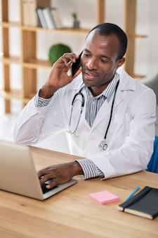 Beau médecin international parlant par téléphone tout en travaillant avec son ordinateur