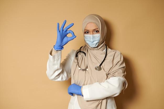 Beau médecin musulman en masque médical couvert la tête en hijab posant sur une surface beige avec copie espace et faisant des gestes ok avec ses doigts
