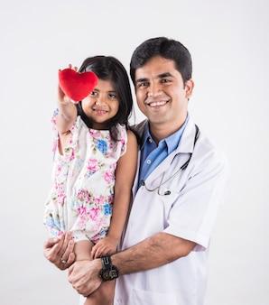 Beau médecin pédiatrique tenant une petite fille patient tenant un jouet coeur en peluche rouge, isolé sur fond blanc