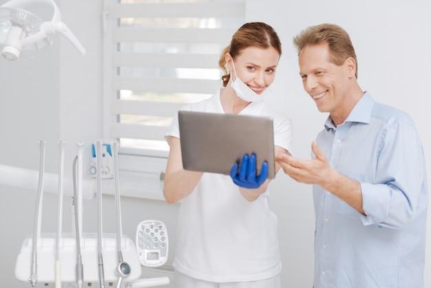 Beau médecin professionnel intelligent utilisant le gadget pour montrer à sa patiente les progrès de son traitement et expliquer comment les choses fonctionnent