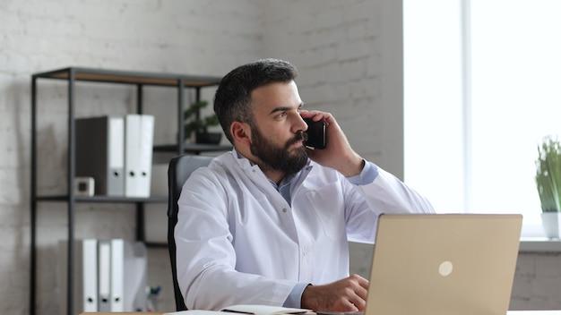 Beau médecin de sexe masculin au bureau a une conversation avec le patient sur smartphone.