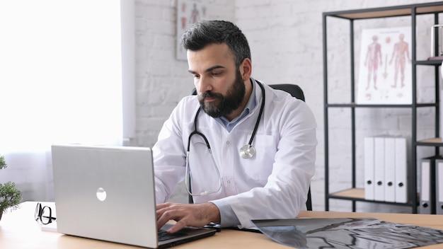 Beau médecin de sexe masculin travaillant avec un ordinateur portable dans un cabinet médical