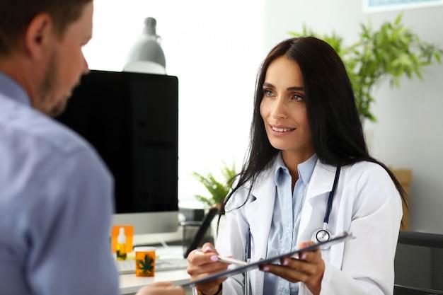 Beau médecin souriant offrant un document de signe visiteur attaché à un tampon