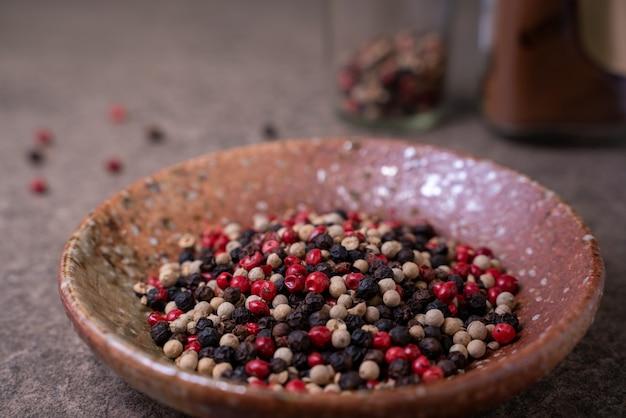 Le beau mélange d'épices est composé de grains de poivre noir, rouge, vert et blanc dans un petit bol sur une table rustique