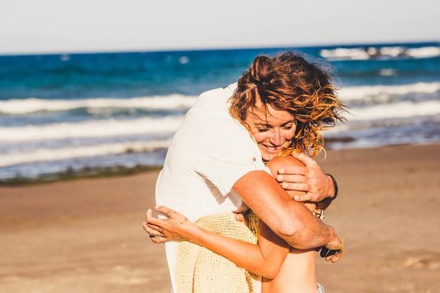 Beau et mignon couple de deux adultes ensemble à la plage étreint avec amour et passion