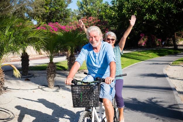 Beau et mignon couple de femme mûre et âgée et homme chevauchant ensemble un double vélo dans un parc verdoyant avec des fleurs roses à l'arrière-plan. senior actif s'amusant avec tandem