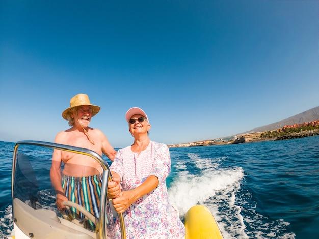Beau et mignon couple de seniors ou de personnes âgées au milieu de la mer conduisant et découvrant de nouveaux endroits avec un petit bateau. femme mature tenant un téléphone et prenant un selfie avec son mari