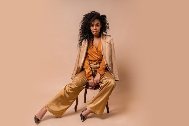 Beau modèle africain avec des cheveux bouclés parfaits dans un élégant chemisier orange et un pantalon en soie assis sur un mur beige de chaise vintage.