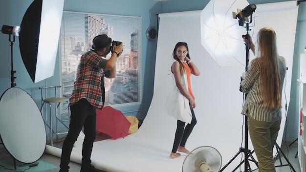 Beau modèle africain posant pour une séance photo pendant que l'assistant ajuste l'éclairage