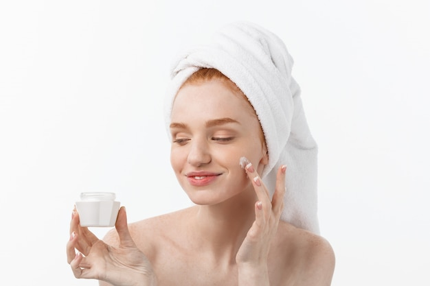 Beau modèle appliquant un traitement de crème cosmétique sur son visage sur blanc.