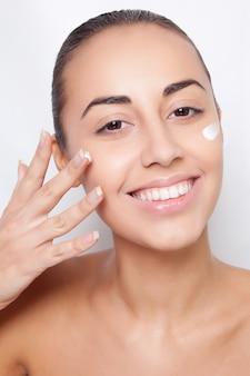 Beau modèle appliquant un traitement crème cosmétique sur son visage