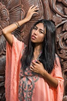 Beau modèle asiatique en robe boho rose posant sur un mur ornemental en bois.