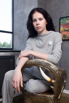 Beau modèle aux cheveux bruns assis dans une chaise design en forme d'éléphant à la maison portant des vêtements informels gris.