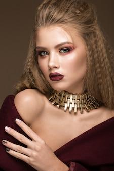 Beau modèle blond avec maquillage lumineux, bijoux en or et lèvres rouges.