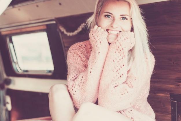Beau modèle blond peau caucasienne blanche avec un visage de beauté vous sourit en regardant la caméra. asseyez-vous dans une camionnette avec un intérieur en bois prêt à parcourir le monde et à vivre en toute indépendance et liberté