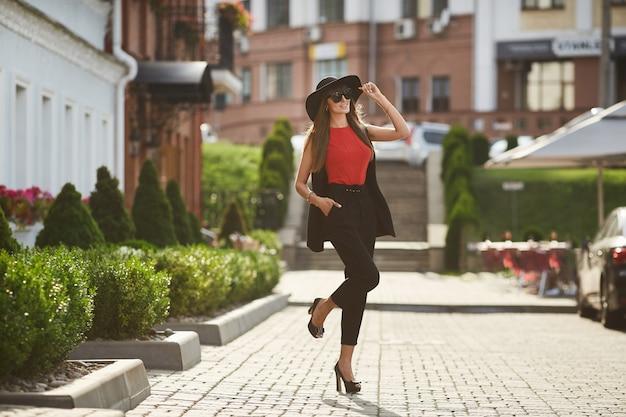 Beau modèle brune femme avec un corps parfait dans le chemisier rouge et dans le costume noir à la mode en ajustant son élégant chapeau noir, sourit et posant dans la rue ensoleillée de la ville