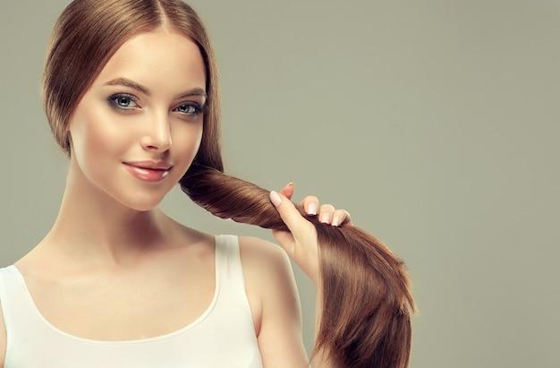 Beau modèle avec des cheveux longs, denses et raides et un maquillage vif, tient dans la queue de paume de cheveux bien coiffés et sains.