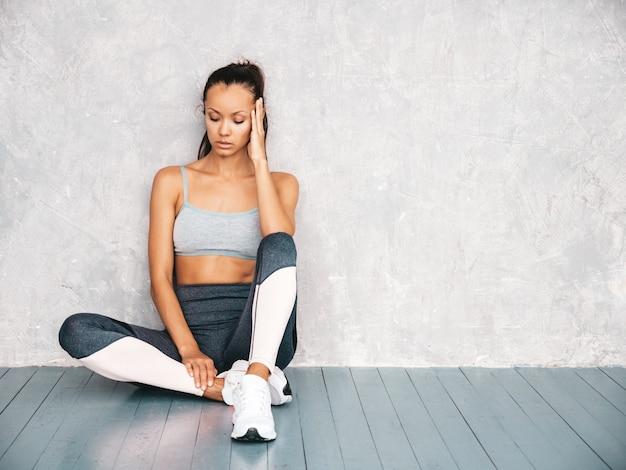 Beau modèle avec un corps bronzé parfait femme assise en studio près du mur gris
