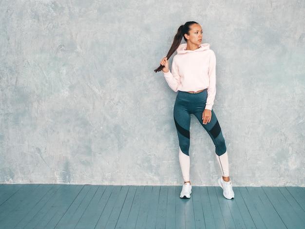Beau modèle avec un corps bronzé parfait. femme posant en studio près du mur gris
