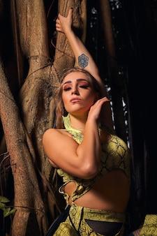 Beau modèle en costume imprimé serpent jaune posant dans la forêt tropicale