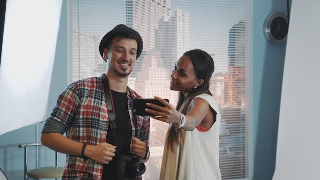 Beau modèle faisant selfie avec beau photographe en studio professionnel