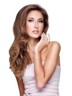 Beau modèle de fasion avec de magnifiques cheveux longs et maquillage posant