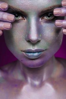 Beau modèle féminin avec art corporel coloré brillant poire sur le visage et le corps