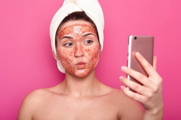 Beau modèle féminin a un masque de gommage sur le visage, enveloppé dans une serviette, pose à moitié nue, prenant selfie sur smartphone, isolé sur rose, se sent émotionnel, garde les lèvres arrondies. concept de cosmétologie