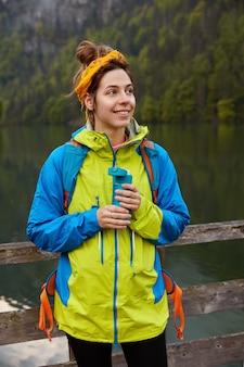 Un beau modèle féminin optimiste trecks en plein air avec des paysages impressionnants