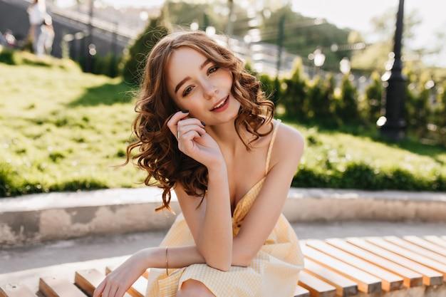 Beau modèle féminin porte une robe jaune s'amusant dans le parc. portrait en plein air d'une jeune femme heureuse au gingembre se détendre sur la nature le matin.