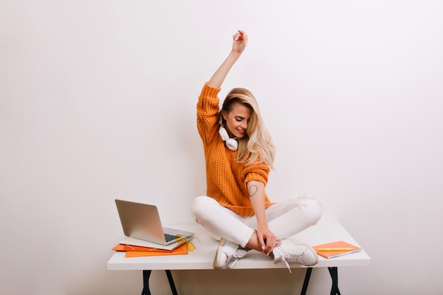 Beau modèle féminin posant près du mur blanc après un long travail avec un ordinateur portable