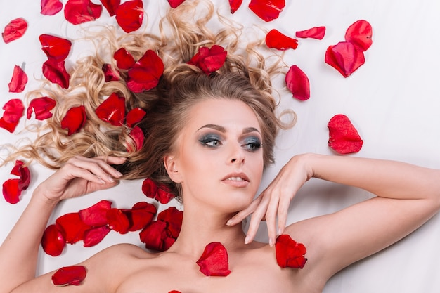 Beau modèle féminin relaxant dans le centre de bien-être, allongé parmi les pétales de rose. soins de la peau et concept de mode de vie sain