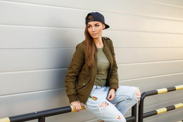 Beau modèle féminin avec des taches de rousseur dans une casquette de baseball dans une veste verte