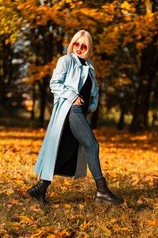 Beau modèle de femme d'affaires avec des lunettes de soleil dans des vêtements à la mode avec des bottes se promène dans le parc sur fond de feuillage d'automne orange au coucher du soleil