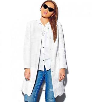 Beau modèle de femme brune dans des vêtements d'été hipster décontracté isolé sur blanc dans des lunettes de soleil