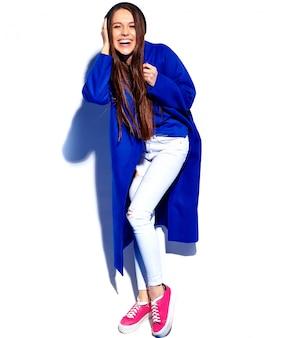 Beau modèle de femme brune hipster souriant en élégant manteau bleu isolé sur blanc. toute la longueur