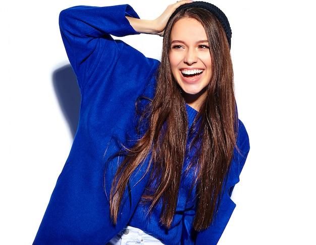 Beau modèle de femme brune hipster souriant en élégant pardessus bleu isolé sur blanc
