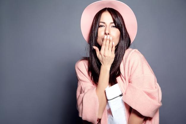 Beau modèle de femme brune hipster souriant en pardessus rose élégant et chapeau coloré posant sur gris. donner un baiser