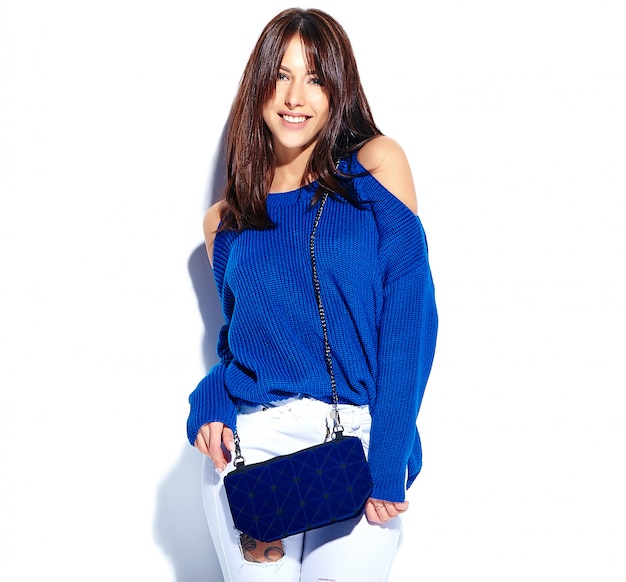 Beau modèle de femme brune hipster souriant en pull d'été élégant décontracté et sac à main bleu isolé sur fond blanc