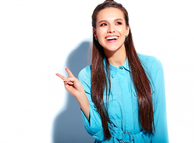 Beau modèle de femme brune souriante caucasienne en robe élégante d'été bleu vif isolé sur fond blanc. montrant le signe de la paix