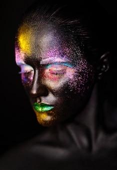 Beau modèle femme avec un masque noir inhabituel en plastique créatif maquillage coloré lumineux avec visage noir