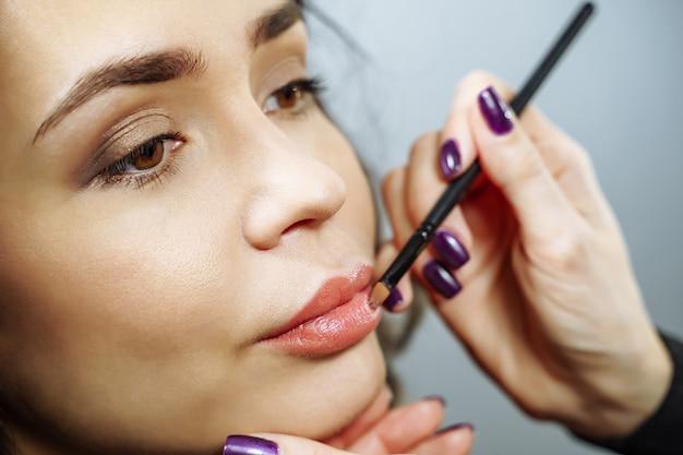 Beau modèle fille appliquant le brillant à lèvres. rouge à lèvres. maquillage professionnel.