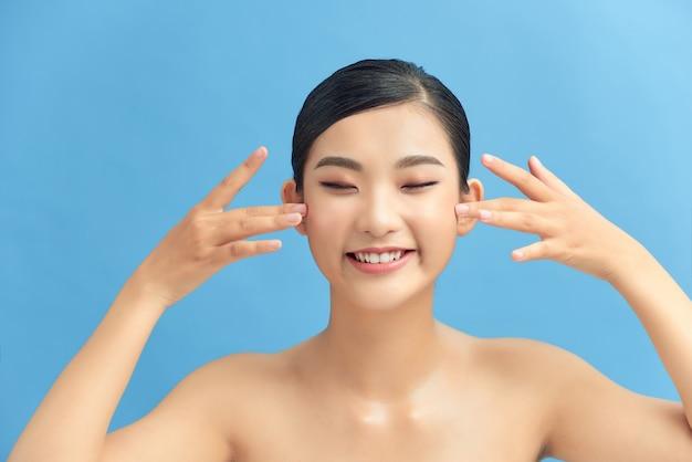 Beau modèle de fille asiatique souriante avec un maquillage naturel touchant une peau hydratée éclatante sur fond bleu en gros plan