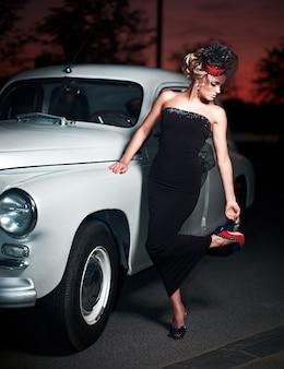 Beau modèle de fille blonde fashion sexy avec maquillage lumineux et coiffure frisée dans un style rétro assis dans une vieille voiture