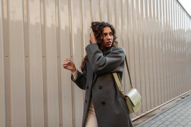 Beau modèle de fille bouclée avec un long manteau vert à la mode avec un sac marche dans la rue près d'un mur en métal