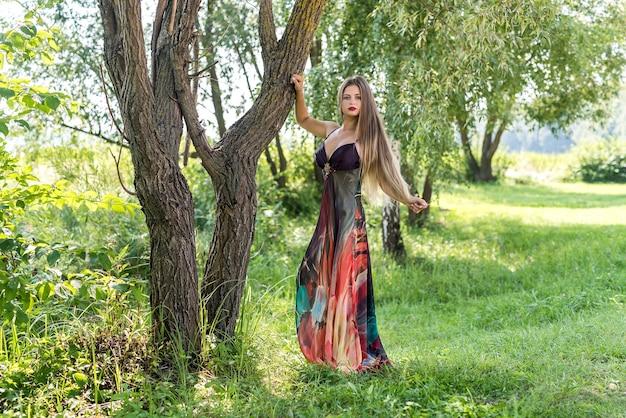 Beau modèle habillé en robe à la mode posant à l'extérieur